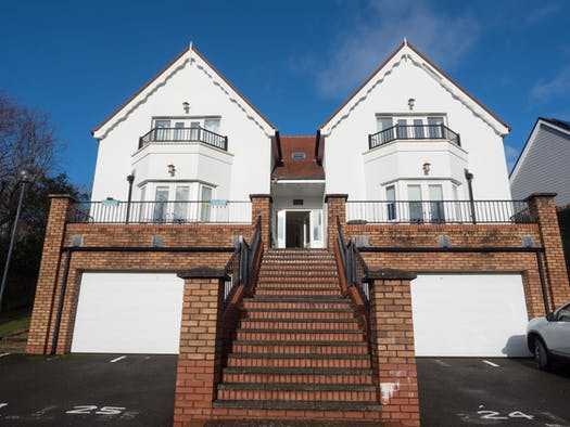 The outside of Caldey House with steps running up to the front door and garages beneath