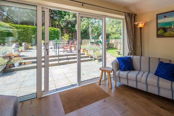 Sofa, stool, patio doors to patio area