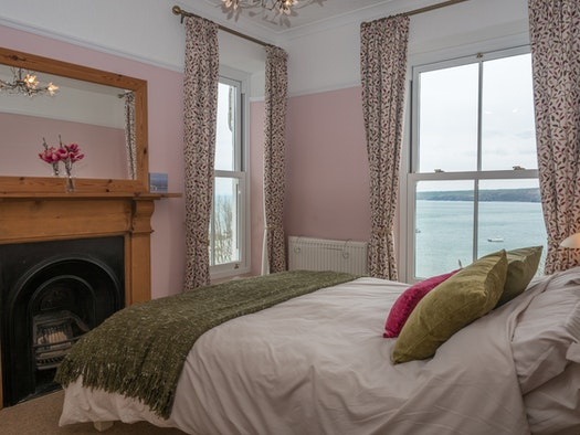 King size bedroom in Glanydon with bed, mirror over the fireplace, 2 windows with sea views