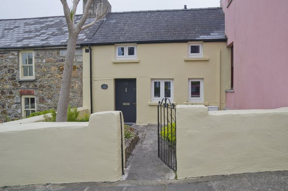 The outside of Cosy Cottage with walled around the garden and a garden gate