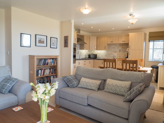 Bright living room in St Brides View with sofas, dining table, chairs and kitchen