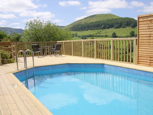 Swimming pool surrounded by decking, table and chairs and beautiful views