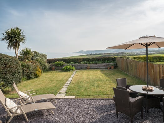 The Garden at Seascape, patio table, umbrella and chairs and lawn to the sea view