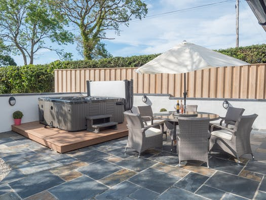 Hot tub, patio table, chairs and umbrella in the garden
