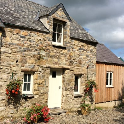 Front of Yr Hen Parlwr, front door, wood clad extension, cobbled yard