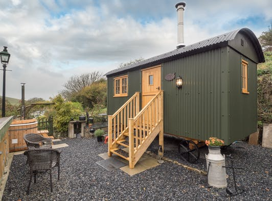Shepherds hut with steps leading to front stable door, hot tub, gravel patio area