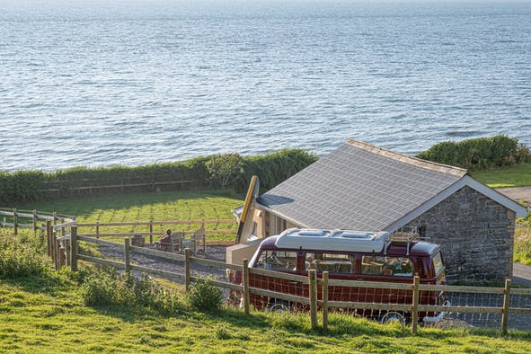 The Greenhouse cottage outside view, campervan, fields and sea