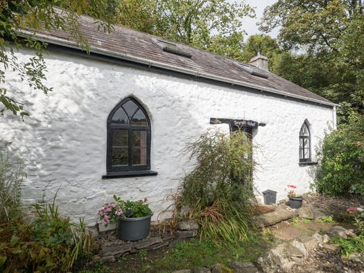 Tanyrallt Uchaf outside view, front door, two arched windows, gardens