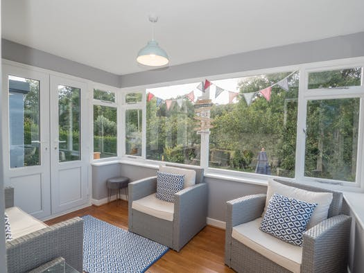 Glenview conservatory with wood floor, 2 seater sofa and two wicker armchairs. Views to the garden