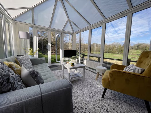 Conservatory lounge area with sofa, coffee table, tv