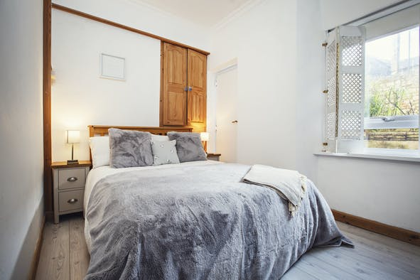 Double bed, with blanket and cushions draped over, bedside cabinets and lamps and storage cupboard