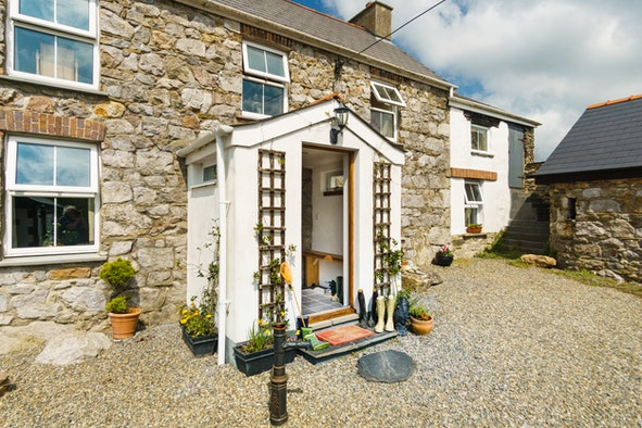 Front porch of house, wellies and door mat at front door, gravel yard to front