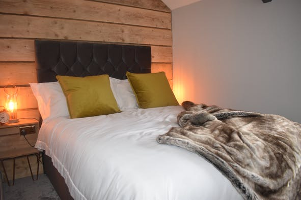 Double bed, with throw, bedside cabinets and lamps