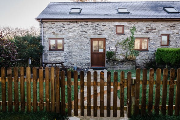 The outside of Red Kite Lodge with picket fence around the garden
