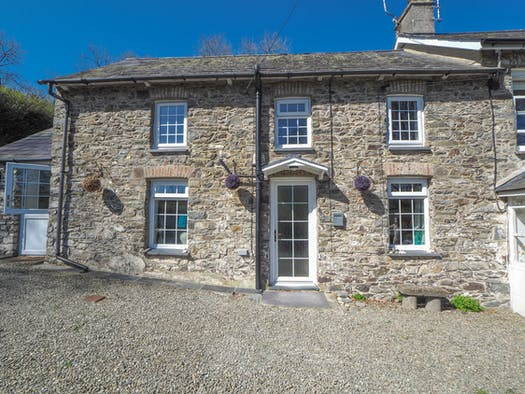 The front of Ty Newydd with gravel floor and stone seat