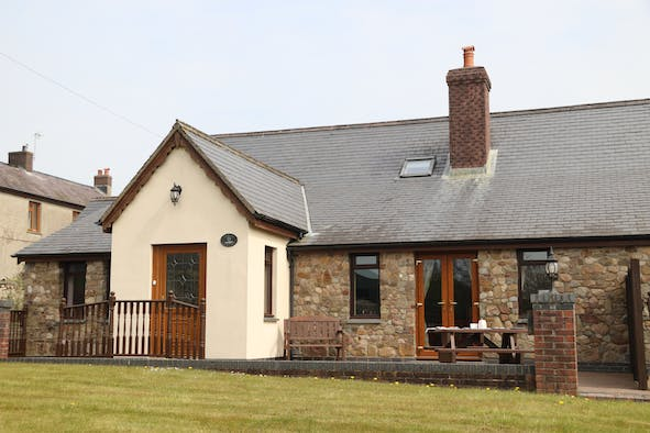 Outside view of Rowan Cottage, lawn, front door, picnic bench and seat