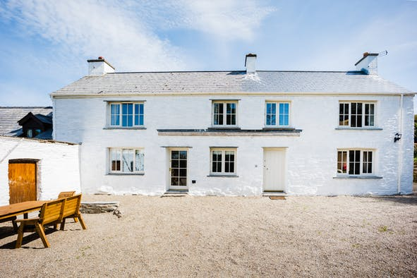 Bayvil. White washed walls. Gravel drive. Wood garden table and chairs