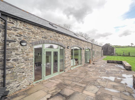 Swydd Long Barn patio area leading onto large lawn. Doors leading onto the patio