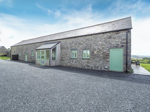Swydd Lond Barn built of stone with green doors and windows and a gravel frontage