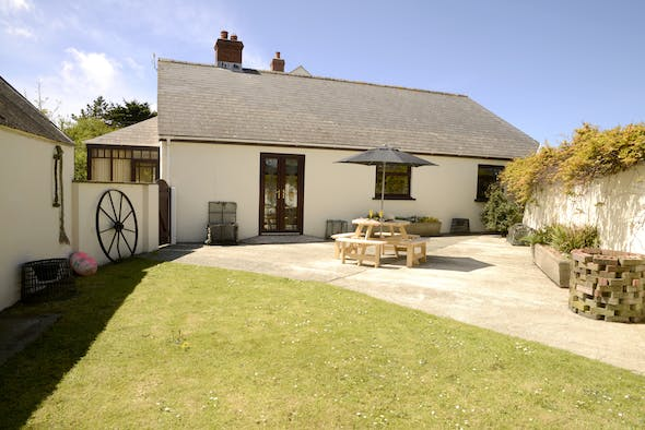 St Brides Cottage with lawn and patio. Wooden patio table and parasol