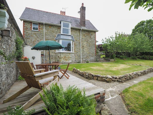 The outside of Glenydd with lawn and furniture on the patio