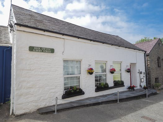 Efail y Mwrthwl Mowr. White walls with window boxes and hanging baskets