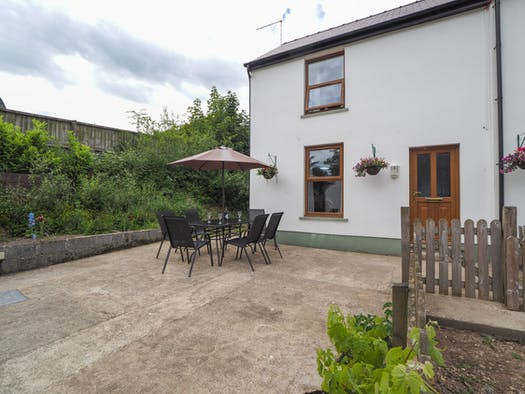 Patio area with outdoor table, chairs and parasol, front entrance to The Swallows cottage