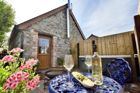Ty Hari stone building with blue bistro table and chairs and bottle of wine