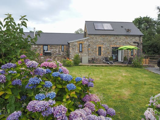Colourful flowers, lawn, chairs and umbrella in front of Sylen Barn