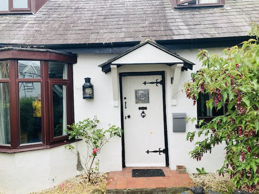 Front door at the Hobbit House, front step, bay window, gravel path and shrubs
