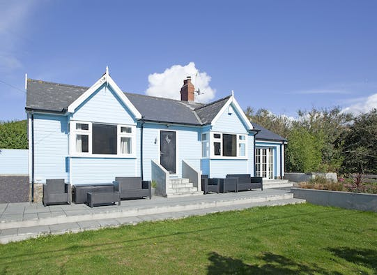 The front of Blue Lodge with steps up to the door and garden furniture under the windows