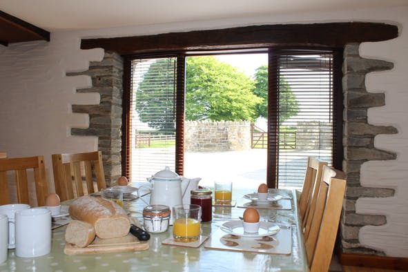 Dining set for breakfast with chairs and doors leading to outside yard