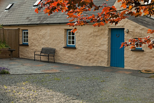 Outside view of Cross Cottage showing gravel yard, front door and bench