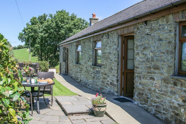 Outside view of Y Dderwen cottage, patio with small table and chairs, front door