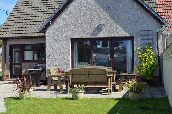 Enclosed garden with patio area, table and chairs, barbecue, lawn and potted plants