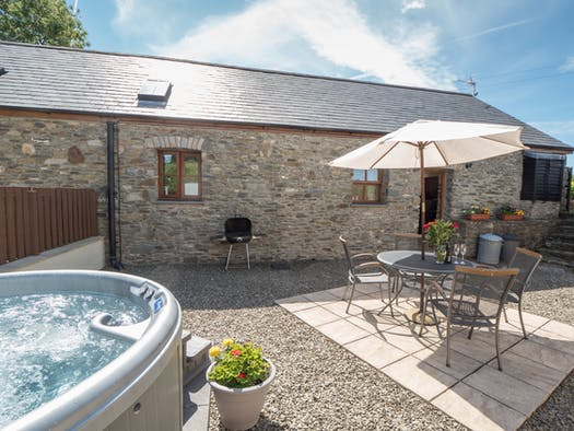 Eirlys patio with hot tub, table and chairs, barbecue and pots of flowers