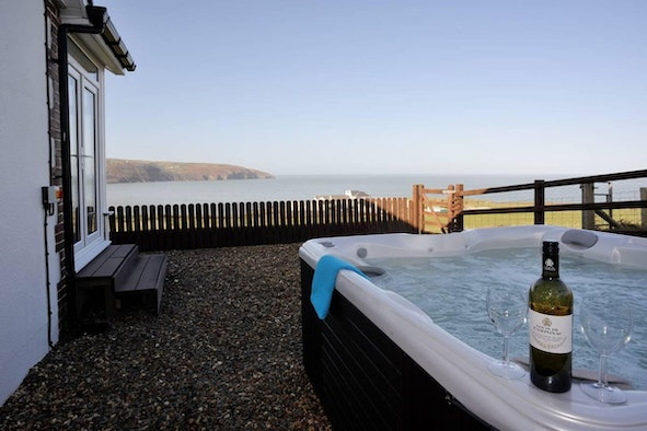 Hot tub with wine and glasses and view to the sea