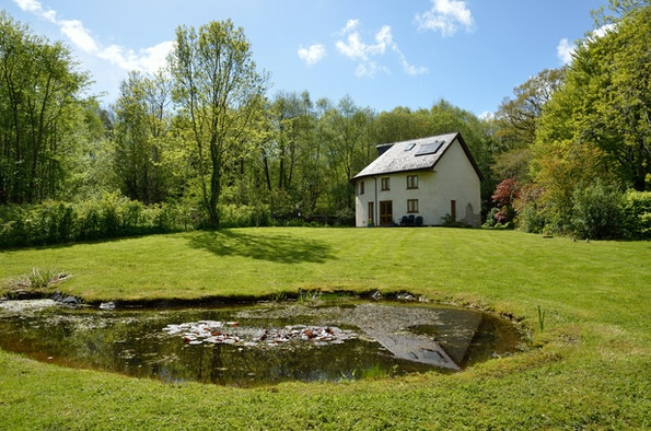 Henllys Lodge from the garden with the wild life pool in the foreground and large lawned area