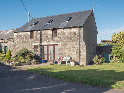 y cartws. stone walls with large front door. a garden bench surrounded by lawns and shrubs