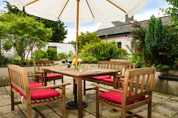 Penyrally patio with table and chairs adjacent to the cottage
