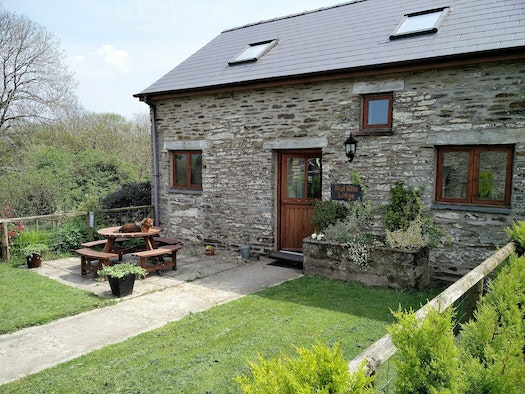 Cottage garden to front with picnic bench, front door, dog sitting on table