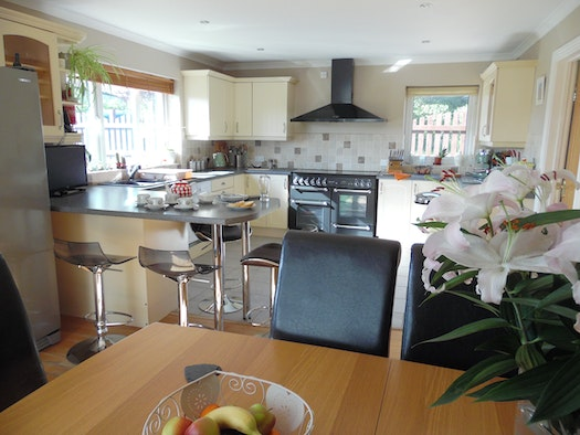 Kitchen/dining area with dining table and chairs, breakfast bar and stools to seat 4