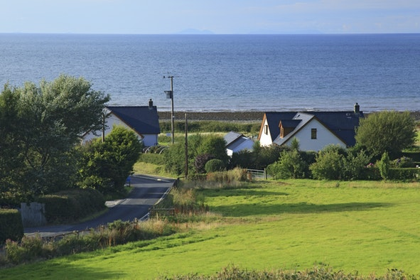 View across fields to cottage with sea beyond