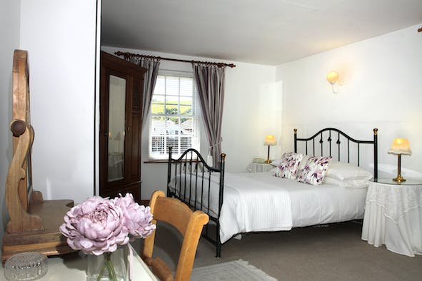 Double bed, bedside table and lamp, dressing table and flowers
