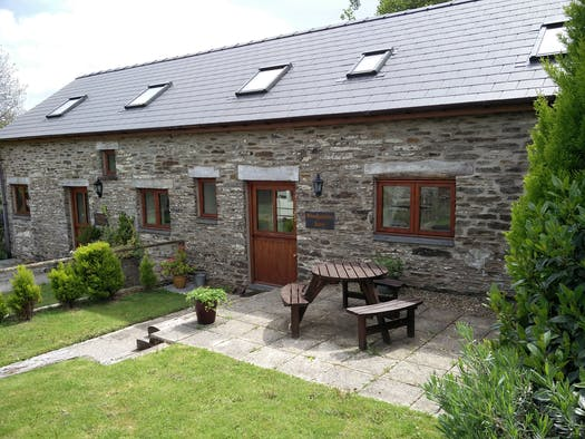 Garden with picnic table and chairs cottage front door behind