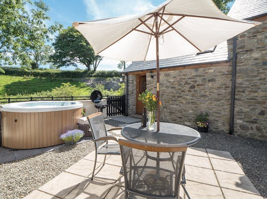 Private patio at Briallen with hot tub, table and chairs